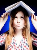 Confused and puzzled young girl holding exercise book on her head Stock Photo