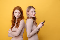 Confused redhead lady near blonde happy woman chatting. Photo of confused redhead lady standing near blonde happy women chatting by phone over yellow background royalty free stock images