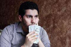 Confused sad arab young businessman with dollar bill. Arab young muslim business man feeling sad and confused with dollar bills in his hand and thinking Royalty Free Stock Photo