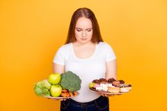 Confused sad upset woman wearing white tshirt can`t make a choic. E between healthy and unhealthy food, she is holding two plates on her hands, isolated on Stock Photography