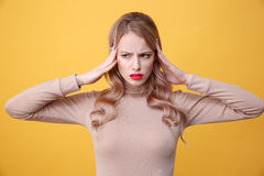 Confused sad young blonde lady with bright makeup lips. Picture of confused sad young blonde lady with bright makeup lips posing over yellow background. Looking Stock Photos