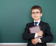 Confused school boy with book portrait, dressed in classic black suit, on green chalkboard background, education and business conc Royalty Free Stock Photo