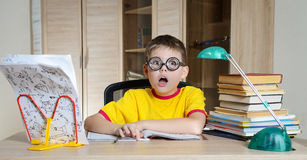 Confused schoolboy in funny glasses screaming near the huge stack of books. Education. Boy Having Problems With His Homework. Royalty Free Stock Images