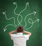 Confused schoolboy. Looking at arrows pointed in different directions, back view stock photos