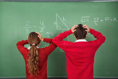 Confused Schoolchildren Standing Against Board Royalty Free Stock Photo