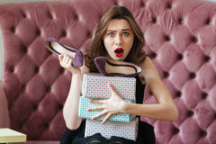 Confused screaming young lady sitting on sofa Stock Images