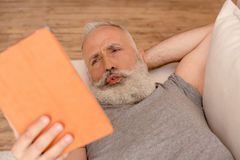 Confused senior bearded man using digital tablet while lying on sofa stock photography
