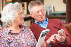 Confused Senior Couple Trying To Operate Mobile Phone Stock Photos