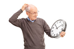 Confused senior holding a big wall clock. And scratching his head isolated on white background Stock Images