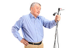 Confused senior holding electronic cables Stock Photo