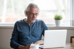 Confused aged man disappointed by negative online news stock images