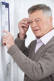 Confused Senior Man With Dementia Looking At Wall Calendar. Confused Senior Man With Dementia Looks At Wall Calendar royalty free stock photo