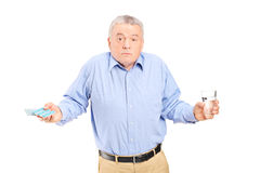 Confused senior man with pills and glass of water stock photo