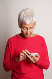 Confused senior woman using smartphone Stock Photo