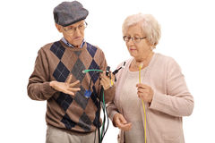 Confused seniors looking at different types of electronic cables Royalty Free Stock Image