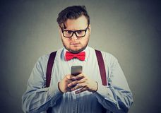 Confused serious looking man thinking what to reply to received text message on cell phone. On gray wall background. Face expression royalty free stock photography