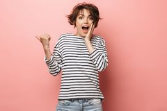 Confused shocked beautiful woman posing isolated over pink wall background pointing royalty free stock photography