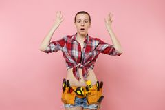 Confused shocked handyman woman in shirt denim shorts, kit tools belt full of variety useful instruments spreading hands. Strong young handyman woman wearing stock photos