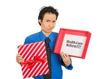 Confused skeptical man holding sign health care reform in gift box royalty free stock photography
