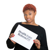Confused, skeptical woman holding sign, health care reform. Portrait young confused, skeptical woman holding sign health care reform, hoping for universal health Stock Images