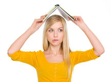 Confused student girl with raised book over head Stock Photo