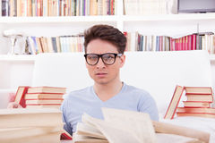 Confused student with glasses studying surrounded by books Stock Photography