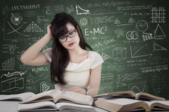 Confused student reading many books. Confused female student reading many books for exam in the class Stock Photos