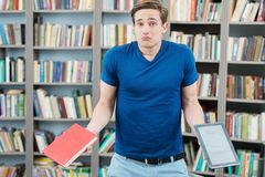 Confused student trying to choose between book and. Portrait of a confused student trying to choose between book and computer Royalty Free Stock Photo