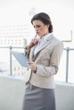 Confused stylish brown haired businesswoman using a tablet pc Royalty Free Stock Photography