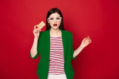 Confused stylish brunette lady with credit card. What does it mean. Waist up portrait of young stylish brunette woman in casual business look being confused royalty free stock image
