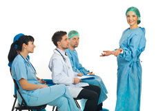 Confused surgeon woman at seminar. Confused surgeon woman don't know what to do at seminar and her colleagues being surprised about her attitude Stock Photography