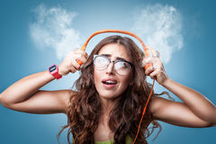 Confused surprised girl in headphones listening to music. Stock Photos