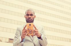 Confused surprised unhappy man using texting on smart phone Stock Photo