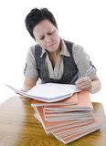 Confused teacher marking students work. In classroom Stock Photo