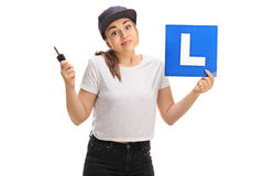 Confused teen girl holding a car key and an l-sign Stock Photography
