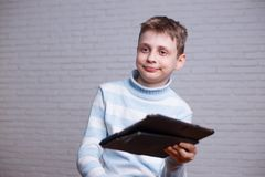 Confused teenage boy with tablet pc in his hands. Technology, so royalty free stock photography