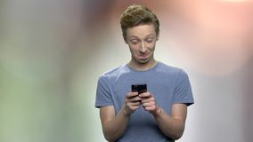 Confused teenage boy using mobile phone. Young trendy boy texting message to girlfriend enjoying free internet connection. Abstract blurred background stock footage
