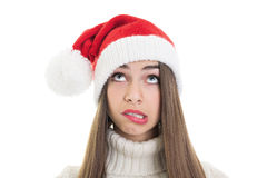 Confused teenage girl wearing Santa beanie hat looking up Royalty Free Stock Photos