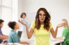 Confused teenage student girl in glasses at school stock photo