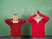 Confused Teenage Students Standing Against Board Stock Image