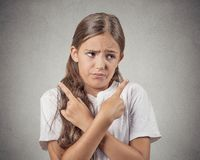 Confused teenager girl pointing in two different directions Royalty Free Stock Photo