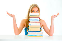 Confused teengirl looking out of pile of book Stock Image
