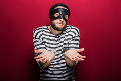 Confused thief with handcuffs. Portrait on red background Stock Photo