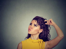 Confused thinking woman bewildered scratching her head seeks solution Royalty Free Stock Photography