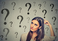 Confused thinking woman scratching her head looking up at many question marks Stock Image