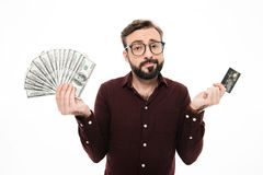 Confused thinking young man holding money and credit card. Photo of confused thinking young man standing isolated over white background. Looking camera holding Royalty Free Stock Photos
