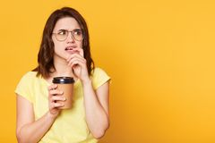 Confused thoughtful young lady looks aside, puts finger in her mouth, holds papercup with coffee in one hand, wearing light yellow stock images