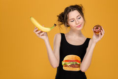 Confused thoughtful young woman choosing between healthy and unhealthy food stock photography