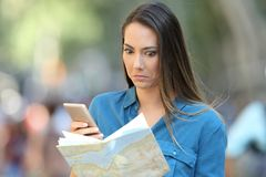 Confused tourist trying to find location. On a map and a smart phone on the street stock images