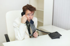 Confused tousled man speaks on phone and chews tie Royalty Free Stock Image